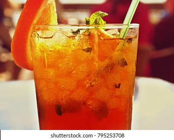 full, transparent glass with a summer cocktail in bright red and golden yellow, on the side there is a straw, on the other side a disc orange. you can clearly see the crushed ice.