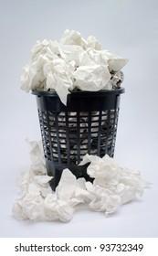 a full trash basket on white background