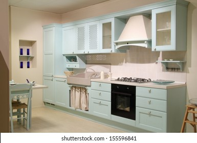 Full view of a country style cyan kitchen with complete furniture.