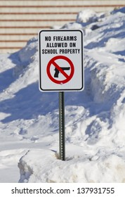 Full View of No Firearms Allowed on School Property Sign outside a school in the snow.