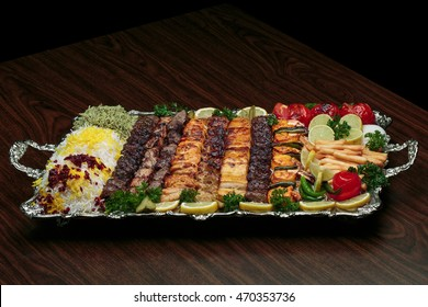 Full view of Persian Mix Kebab of minced meat and chicken With Rice and french fries and vegetables in a large traditional tray on wooden table