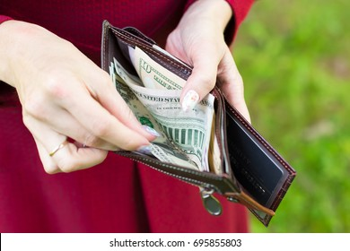 Full wallet with money in the hands of a woman