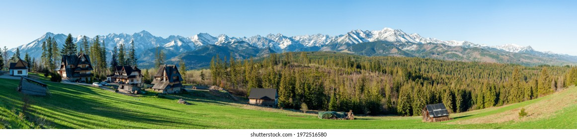 Full wide panorama of the Tatra Mountains viewed from Głodówka glade in Poland with typical Polish highlanders'  houses. Early morning in spring