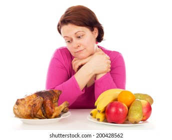 Full woman thinks to eat chicken or fruit, isolated on white background