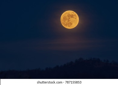 Full yellow moon over the hills in the first day of the year