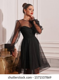 Full-body portrait of beautiful young woman with hair bun wearing black chiffon cocktail dress and high heels and posing in exquisite apartment. Magnificent brunette model in classy evening outfit.