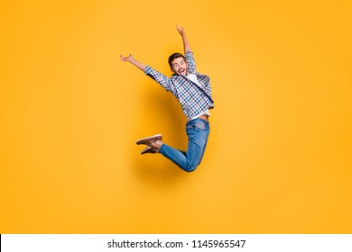 Full-body portrait of flying and cheerful man in sneakers, denim outfit, jumping with raised arms isolated on shine yellow background