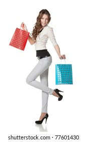 Full-body portrait of young elegant female holding paper-bags with purchases isolated on white