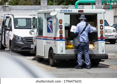 Fullerton, California / USA - August 13, 2020: A USPS (United States Parcel Service) mail truck and postal carrier make a delivery.
