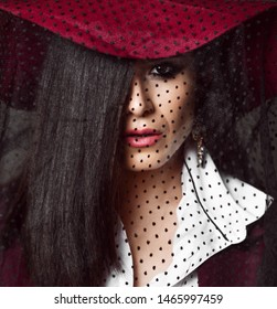 Full-face portrait of mysterious lady brunette in dark red hat with her veil down and with half face hidden by her long straight hair
