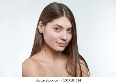 Fullface type half profile portrait of a young beautiful brunette model with green eyes being naural and without makeup on her face. Photo made on a white background in a professional photo studio.