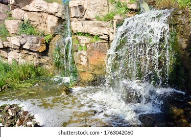 full-flowing waterfall by the river, hidden in the forest