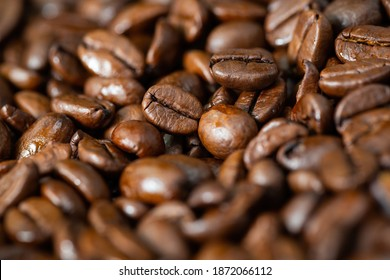 Fullframe of dark roasted coffee beans from close up. Coffeine aromatic brown seeds in focus on background. Heap of textured energy grains as backdrop.