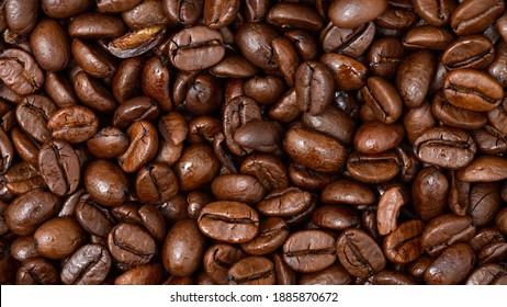 Fullframe shot of fresh roastend coffee beans zoom in. Aromatic brown textured seeds on background from close up. Black energy structured grain on backdrop.