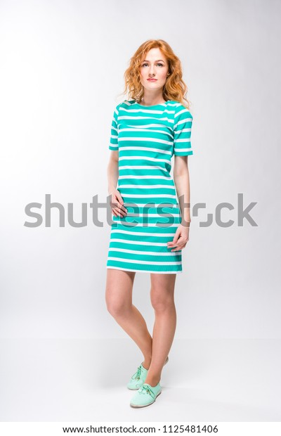 full-height portrait of a young, beautiful woman with red curly hair in a summer dress with strips of blue in the studio on a gray background. Theme of summer vacation, tourism and summer clothes.
