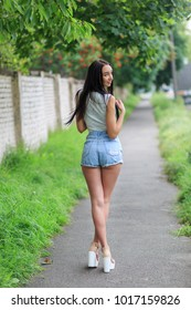 A full-height vertical shot of young adult woman standing in a green alley with long dark hair wearing cropped shirt high-waisted jean jeans and high-heel pumps