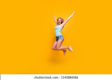 Full-legh portrait of cute blondy girl happily jump and rejoices of victory rise up fists isolated on bright yellow background with copy space for text