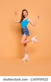 Full-legs vertical portrait of stylish and cheerful girl pleased with the beginning of the roller-skating season by raising her hands up and smiling broadly isolated on yellow peach background