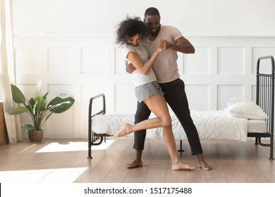 Full-length african young active couple in love wearing comfortable home clothes holding hands dancing in the morning at sunny summer day standing barefoot in bedroom, activity, fun and hobby concept