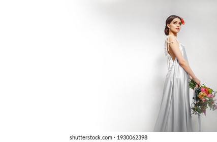 A full-length bride in a wedding image against a white wall. A gray shiny dress and a red flower in her hair