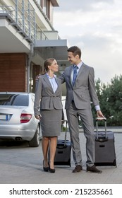 Full-length of business couple walking with luggage outside hotel