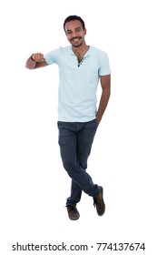 Full-length of cheerful brown skinned male with a hand in pocket, wearing a light blue t-shirt, jeans trousers,  sneakers, and bracelet. Leaning on something beside. Isolated on white background