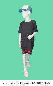 Full-length child mannequin dressed in casual clothes, isolated on green background. No brand names or copyright objects.