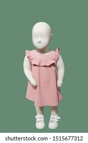 Full-length child mannequin wearing pink dress, isolated on green background. No brand names or copyright objects.