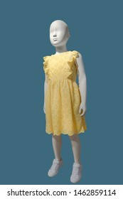 Full-length child mannequin wearing yellow dress, isolated. No brand names or copyright objects.
