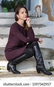 Full-length fashion portrait of a mature woman wearing high knee black boots and a purple dress, sitting outdoors.