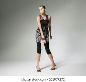full-length fashion shot of girl with posing in light background