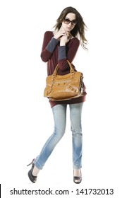 full-length fashion woman in jeans with bag against white background