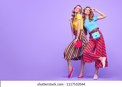 Full-length fashionable Girl with Wavy Hairstyle Having Fun Dance. Young Beautiful Pretty Model Woman in Striped Fashion Stylish Summer Outfit. Crazy funny Sisters Friends on Purple