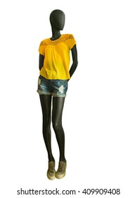 Full-length female mannequin clothing in yellow blouse with embroidery jeans shorts, isolated on white background. No brand names or copyright objects.