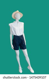 Full-length female mannequin dressed in blouse and shorts. Isolated on green background. No brand names or copyright objects.