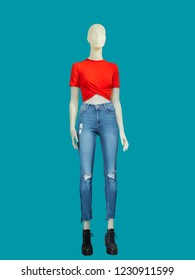 Full-length female mannequin dressed in blue jeans and red top, isolated on blue background. No brand names or copyright objects.
