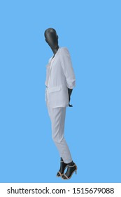 Full-length female mannequin dressed in fashionable white trouser suit isolated on blue background. No brand names or copyright objects.