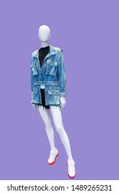Full-length female mannequin dressed in jeans jacket and shorts, isolated. No brand names or copyright objects.
