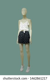 Full-length female mannequin dressed in top and shorts, isolated on green background. No brand names or copyright objects.
