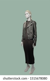 Full-length female mannequin wearing black leather jacket and brown knitted dress, isolated. No brand names or copyright objects.