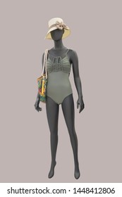 Full-length female mannequin wearing fashionable bathing suit, isolated. No brand names or copyright objects.