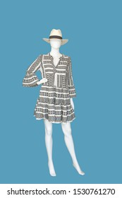 Full-length female mannequin wearing fashionable dress with traditional Greek ornament, isolated on blue background. No brand names or copyright objects.