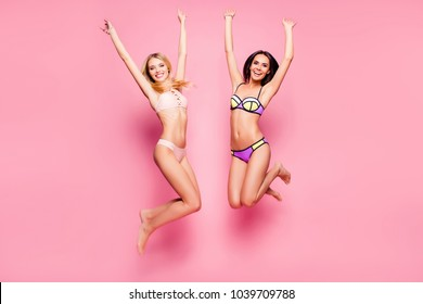 Full-length full-size portrait of two careless cheerful beautiful attractive joyful delightful women dressed in nice swimwear, they are jumping and putting hands up, isolated on bright pink background