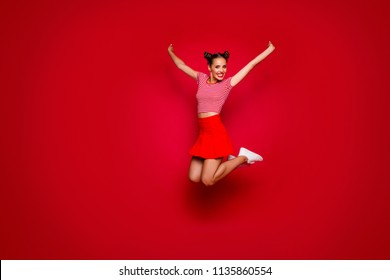 Full-length full-size view of jumping laughing and happy woman dressed in colourful bright clothes isolated on red background