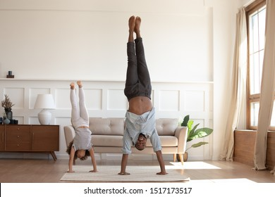 Full-length image african father and little daughter having fun fool around at home sportive active kid girl and dad do handstand position. Funny leisure activities, sporty healthy lifestyle concept