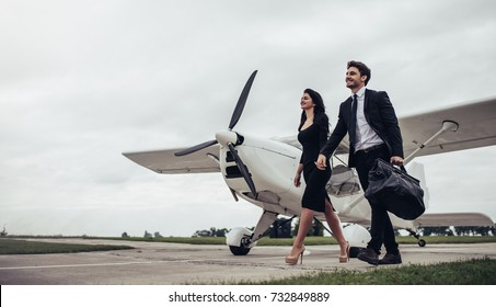 Full-length image of beautiful young stylish couple  in official clothes near private plane. Walking on runway in airport in front of airplane.
