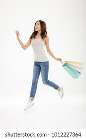 Full-length image of ecstatic adult female levitating or jumping with lots of colorful shopping bags in hand isolated over white background