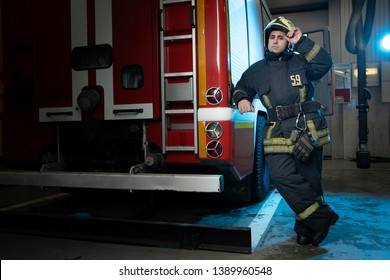 Full-length image of man firefighter at fire truck