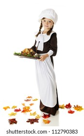 Full-length image of pretty elementary Pilgrim girl carrying a wooden plate of roast bird with veggies.  On a white background.