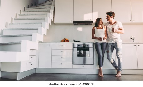Full-length image of romantic couple at home. Attractive young woman and handsome man are enjoying spending time together while standing on light modern kitchen with cup of coffee in hands.